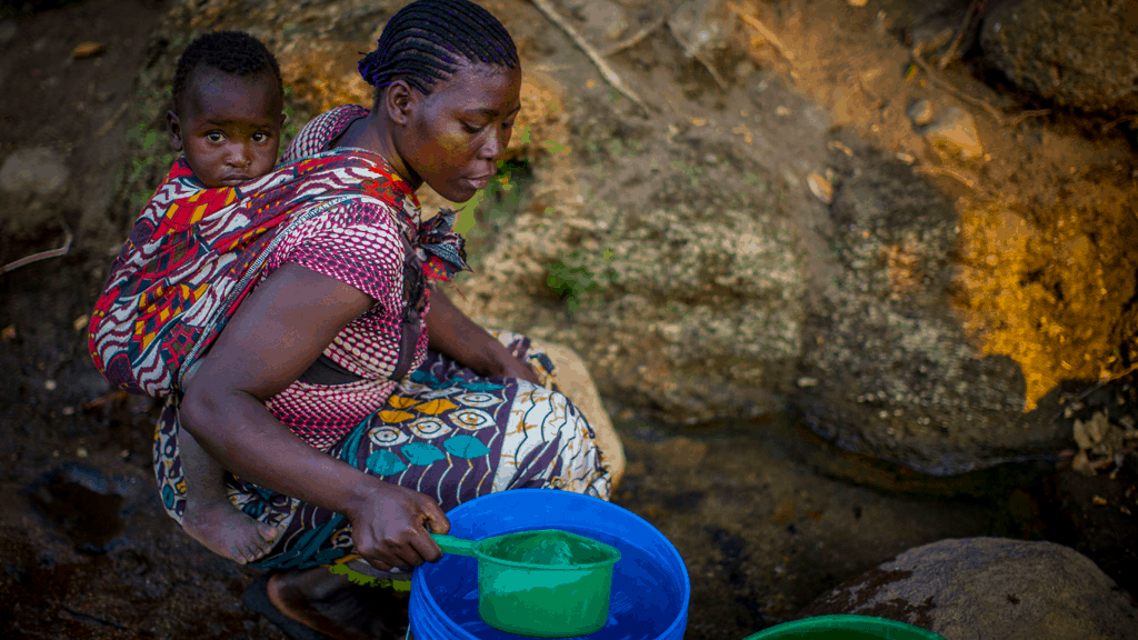 A woman and her young baby collecting water from an open water source