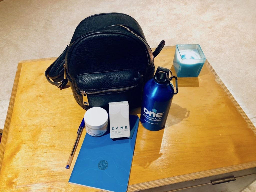 Bag containing a notebook and pen, moisturiser, refillable water bottle and organic tampons