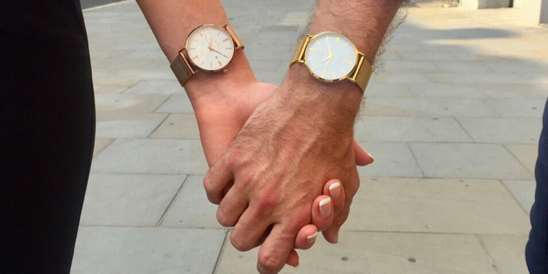 Couple holding hands with watches on