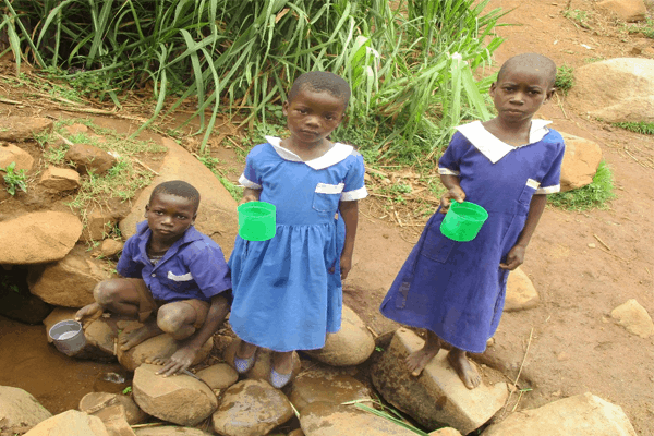 Pupils collecting water from an unprotected shallow well