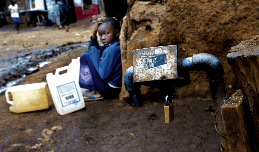 Ann sitting next to a padlocked tap in Nairobi, Kenya