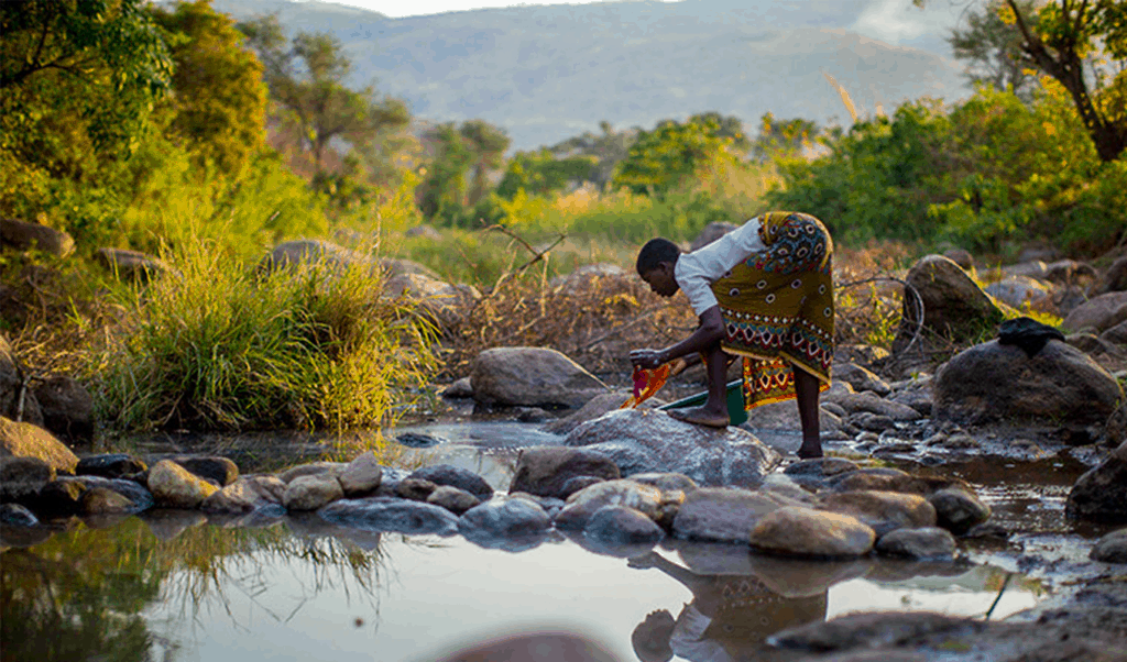 Woman collecting water from open water source