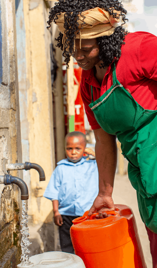 Woman collecting water from community tap