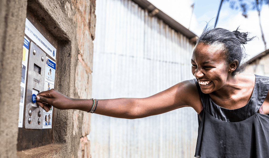 A woman using tap and pay technology to collect her clean water
